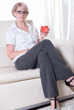 Young attractive woman enjoys a cocktail on the couch Royalty Free Stock Photo