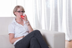 Young attractive woman enjoys a cocktail on the couch Stock Photo