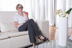 Young attractive woman enjoys a cocktail on the couch Stock Photos