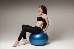 Young attractive woman exersicing with fitness ball Stock Photos
