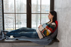 Young attractive woman fall asleep on the windowsill while readi Royalty Free Stock Photo