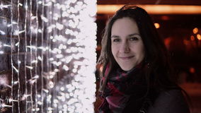 Young attractive woman in the falling snow at Christmas night looking at the camera lights at background Stock Image