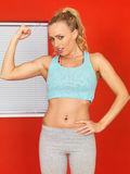 Young Attractive Woman Flexing Her Arm Muscles. Attractive Young Woman with blonde hair, in her twenties, looking at the camera, flexing her developed arm Royalty Free Stock Photography