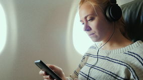 Young attractive woman is flying in an airplane. It uses a smartphone listening to music. On headphones stock video footage