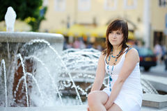 Young attractive woman by a fountain Royalty Free Stock Photos