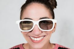 Giggly laughing face with 3d white eyeglasses. Young attractive woman funny close up with white 3d eyeglasses smiling and laughing royalty free stock photos