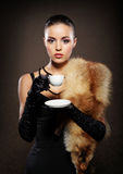 A young and attractive woman in fur drinking a cup of tee Royalty Free Stock Images