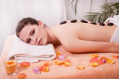 Young attractive woman get hot stone massage Royalty Free Stock Images