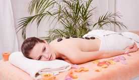 Young attractive woman get hot stone massage Stock Image