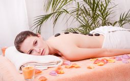 Young attractive woman get hot stone massage Royalty Free Stock Photo