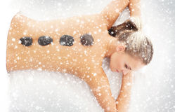 Young attractive woman getting hot stone treatment on the snoe Royalty Free Stock Photo
