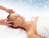 Young attractive woman getting massaging treatment on the snow Royalty Free Stock Images