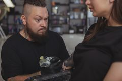 Young attractive woman getting new tattoo by professional tattooist. Bearded mature tattoo artist concentrating, making funny face while working on a tattoo on a royalty free stock photos
