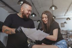Young attractive woman getting new tattoo by professional tattooist stock photos