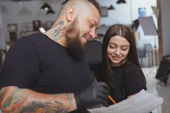 Young attractive woman getting new tattoo by professional tattooist. Cropped shot of a beautiful cheerful young women smiling, deciding which tattoo she wants at stock photo