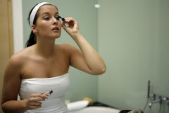 Young attractive woman getting ready in bathroom. Looking into mirror Stock Photos