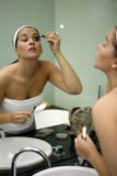 Young attractive woman getting ready in bathroom. Looking into mirror Stock Photography