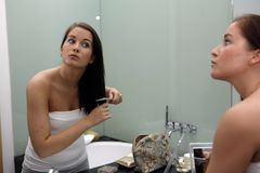 Young attractive woman getting ready in bathroom. Looking into mirror Stock Images