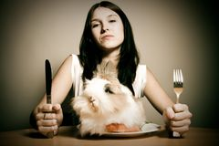 Rabbit For Dinner. A young attractive woman getting ready to enjoy a cute fluffy bunny for dinner. yummy royalty free stock photography