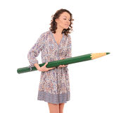 Young attractive woman with giant green pencil Stock Image