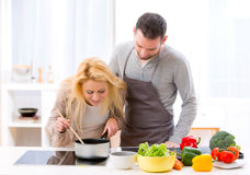 Young attractive woman give food to her husband to taste Royalty Free Stock Photo