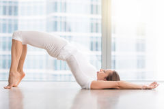 Young attractive woman in Glute Bridge pose against floor window. Young attractive woman practicing yoga, stretching in Glute Bridge exercise, dvi pada pithasana Royalty Free Stock Images