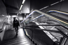 Young and attractive woman is going up the stairs in metro from station to the exit. Black and white photo, perspective lines. Barcelona, Spain royalty free stock image