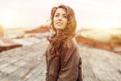 Young attractive woman with good mood enjoying beautiful city landscape while standing on a roof of building, charming smiling hip. Young curly attractive woman stock image