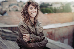 Young attractive woman with good mood enjoying beautiful city landscape while standing on a roof of building, charming smiling hip. Young curly attractive woman royalty free stock photos