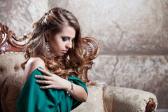 Young attractive woman in green dress sits on a Stock Images