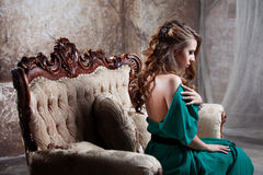 Young attractive woman in green dress sits on a Stock Photo