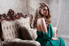 Young attractive woman in green dress sits on a Royalty Free Stock Photos