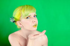 Young attractive woman with green hair sends an air-kiss Royalty Free Stock Photos