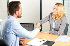 Young attractive woman handshaking at the end of a job interview Royalty Free Stock Image
