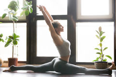 Young attractive woman in Hanumanasana pose, home interior backg Stock Photos