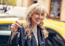 Young attractive woman has a key to the car. She is happy about this Stock Photo