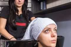 Young attractive woman having her hair wrapped in a towel by fem Royalty Free Stock Photo
