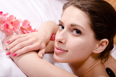 Young attractive woman having spa procedures: stones, flower, happy smiling & looking at camera Stock Images