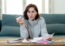 Upset young woman stressed about credit card debts and payments not happy accounting finances. Young attractive woman having trouble with card payments and home stock photography