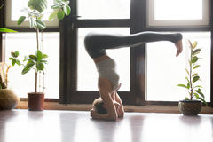 Young attractive woman in headstand pose, home interior backgrou Stock Photo