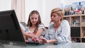 Young attractive woman helping a teenage girl with a text on computer. Mother helping her daughter to write a text stock footage