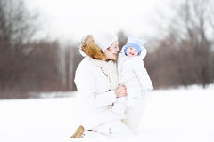 Young attractive woman  with her baby in snowy park Royalty Free Stock Image
