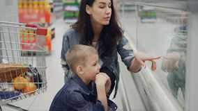 Young attractive woman and her cute blond son are choosing food in supermarket pointing at products and talking. Shopping trolley with bright tasty products is stock footage