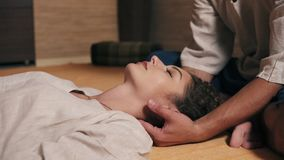 Young attractive woman with her eyes closed is receiving neck massage by male thai massagist. Closeup view. Shot in 4k