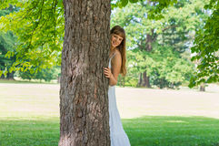 Young attractive woman hiding behind a tree Royalty Free Stock Image