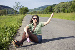 Young attractive woman hitchhiking, sitting on the Royalty Free Stock Photography
