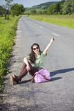 Young attractive woman hitchhiking, sitting on the Royalty Free Stock Photos