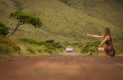 Young bride in white wedding dress on background of beautiful view of Flores island, AzoresYoung woman hitching a ride on a road i royalty free stock photos