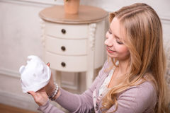 Young attractive woman holding baby hat, interior Royalty Free Stock Photo