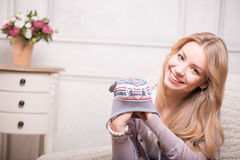 Young attractive woman holding baby hat , interior Stock Photo